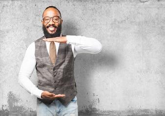 Hombre sonriendo con las manos indicando una medida del tamaño de su camiseta