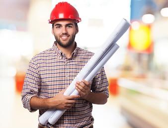 Hombre sonriendo con un casco rojo y unos planos