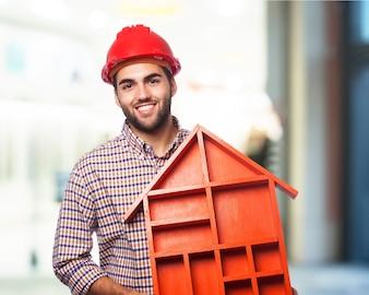 Hombre sonriendo sosteniendo una casa