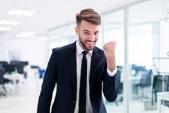 Hombre sonriente elegante con un puño levantado