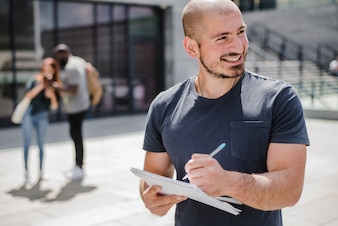Hombre sonriente sosteniendo la escritura del cuaderno