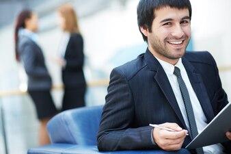 Hombre sonriente sujetando un bolígrafo y una carpeta