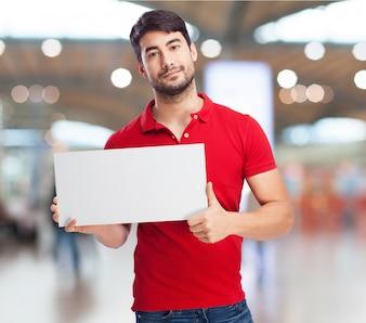 Hombre sonriente sujetando un cartel en blanco