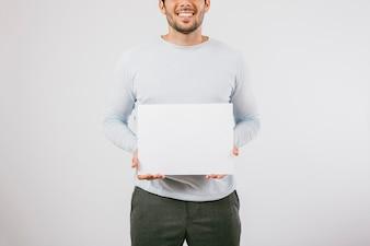 Hombre sonriente sujetando un póster en blanco