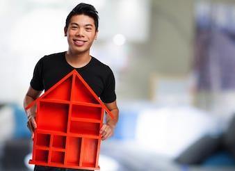 Hombre sosteniendo una casa roja