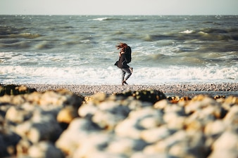 Hombre subiendo a su novia en brazos en la playa