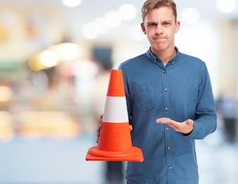 Hombre sujetando un cono naranja