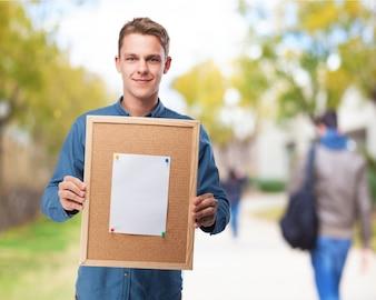 Hombre sujetando un tablón de corcho con una hoja en blanco