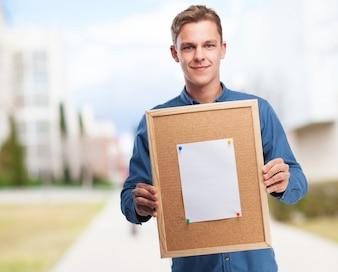 Hombre sujetando un tablón de corcho