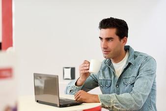Hombre tomándose un café con un portátil