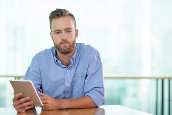 Hombre triste que se sienta en el vector del café y que usa la tablilla