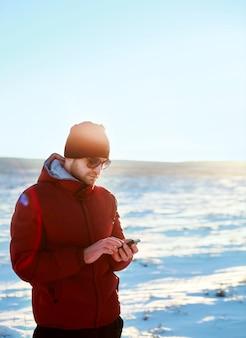 Hombre usando su móvil en el campo cubierto de nieve