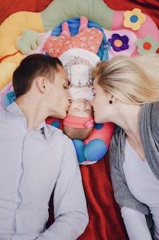 Hombre y mujer besando a su bebé