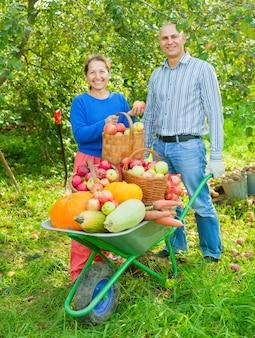 Hombre y mujer con la cosecha en el jardín de verduras