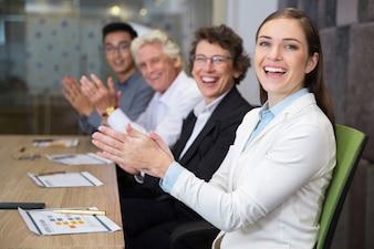 Hombres de negocios alegres que aplauden en la sala de juntas