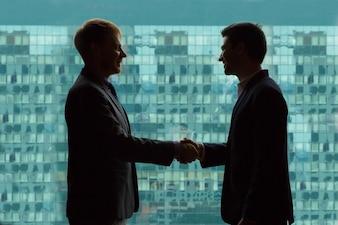 Hombres de negocios dándose la mano con un fondo verde de edificios de oficinas