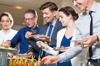 Hombres de negocios felices servirse a sí mismos en el buffet