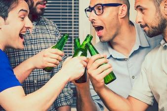 Hombres felices bromeando y brindando con botellas de cerveza