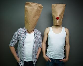 Hombres jóvenes con bolsas de papel sobre sus cabezas