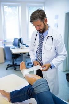Hombres médico de vendaje del pie del paciente femenino
