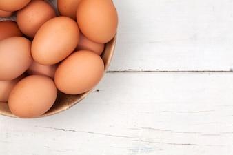Huevo de pollo en el tazón de madera en la mesa de madera con espacio para copiar.