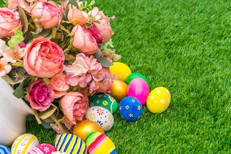 Huevos de Pascua con la flor artificial de la hierba verde fresca