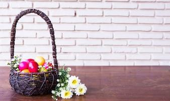 Huevos de pascua de colores en la cesta marrón con flor