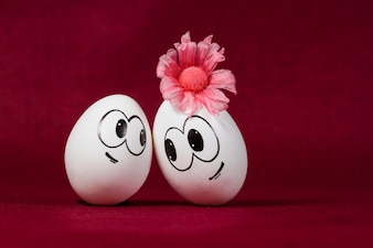 Huevos sonrientes sobre fondo granate
