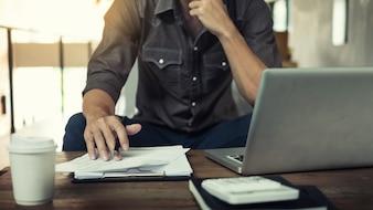 Imagen auténtica de un hombre de negocios pensativo en una cafetería sentada en el café y el trabajo