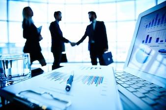 Información económica con ejecutivos negociando de fondo