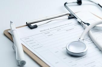 Informe de examen médico y estetoscopio en blanco de escritorio