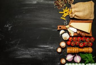 Ingredientes para hacer pasta con tomate y queso sobre una mesa negra