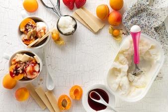 Ingredientes sabrosos apetitosos para cocinar el helado de vainilla con las cucharas y las frutas del helado. Vista superior con espacio de copia.