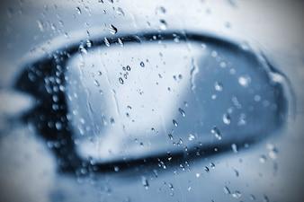 Invierno coche, el concepto de paseo en coche de invierno. Espejo y hielo y gotas de agua en el parabrisas.