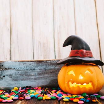 Jack-o-linterna en sombrero de bruja y caramelos