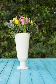 Jarrón blanco con flores de colores al aire libre