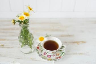 Jarrón decorativo junto a una taza de té