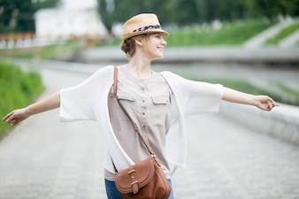 Joven alegre mujer feliz viajero en sombrero de paja disfrutando de su viaje