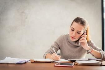Joven atractiva chica hablando por teléfono móvil y sonriendo mientras está sentado solo en cafetería durante el tiempo libre y trabajando en la computadora tablet. Hembra feliz que tiene resto en café. Estilo de vida.