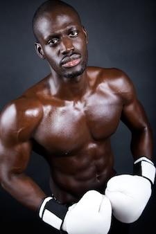 Joven boxeador atlético con guantes en fondo negro.
