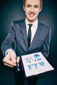 Joven empresario sujetando un bolígrafo y una carpeta con un informe