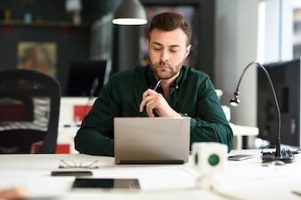 Joven estudiando con ordenador portátil en el escritorio blanco.