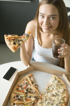Joven feliz niña con una rebanada de pizza
