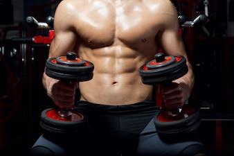 Joven haciendo ejercicio de peso pesado en el gimnasio.