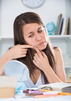 Joven hembra es exprimir una espinilla antes de maquillaje