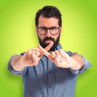 Joven hombre hipster haciendo NO gesto sobre fondo de colores