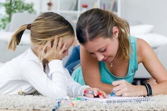 Joven madre e hija de dibujo en el bloc de notas en casa.