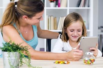 Joven madre e hija jugando con la tableta digital en casa.