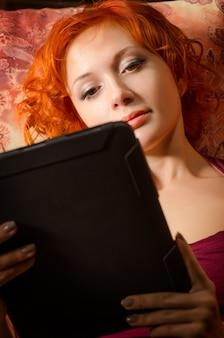 Joven mujer en un sofá con Tablet PC
