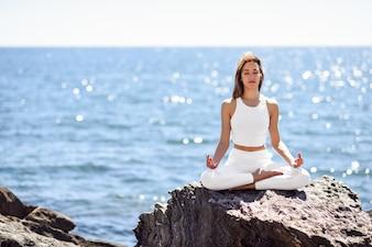Joven mujer haciendo yoga en la playa